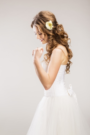 dress up: Studio portraits with beautiful bride isolated on gray