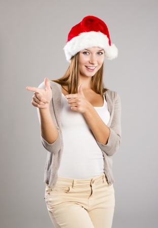 Portrait of attractive woman isolated on gray, studio shot in christmas hat photo