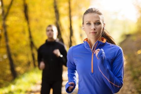 Jonge lopende paar joggen in de herfst de natuur