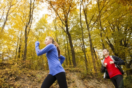 Young running couple jogging in autumn nature photo