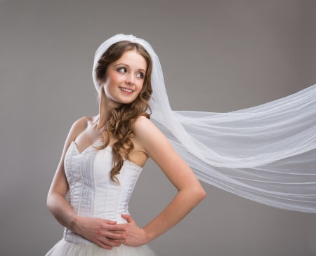 Portrait of beautiful bride with veil isolated over gray background photo