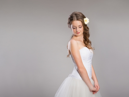 Portrait of beautiful bride posing isolated over gray background photo