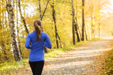 Bautiful running woman jogging in autumn nature Stock Photo