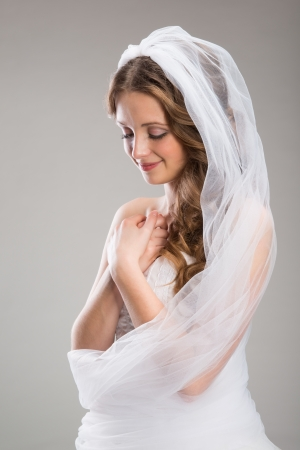 veiled: Portrait of beautiful bride with veil isolated over gray background Stock Photo