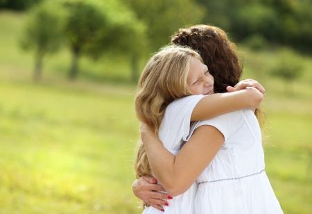 madre e hija adolescente: Madre y abrazando a su hija adolescente y sonriendo juntos en el jardín de verano Foto de archivo