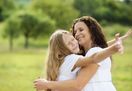 Mother and teenage daughter hugging and smiling together in summer garden  photo