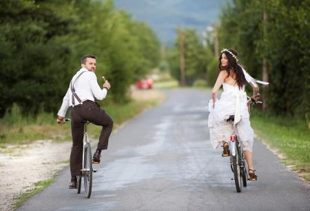 Mooie bruid en bruidegom rijden op de fiets Stockfoto