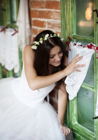 Beautiful bride in country style wedding dress is looking out of the window photo