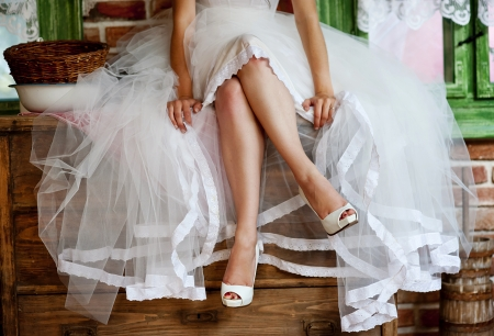 bridal: Detail of bridal legs with shoes sitting on the wooden table