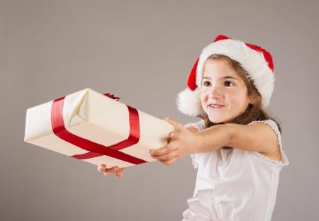 dar un regalo: La pequeña muchacha feliz en el sombrero de santa con el regalo de navidad