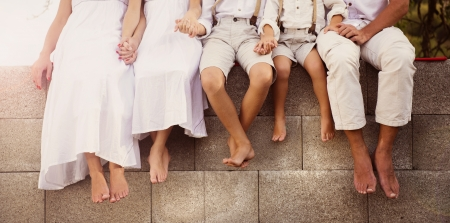 bare feet boys: Family is sitting on the fence with the detail of bare feet Stock Photo