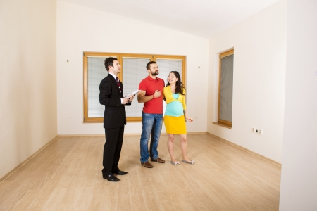 selling house: Young couple is sitting on the floor in their empty new house  Woman is pregnant