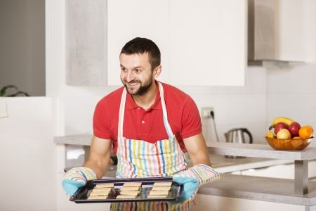 funny fruit: Young man with apron is cooking in the kitchen