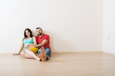 Young couple is sitting on the floor in their empty new house  Woman is pregnant  photo