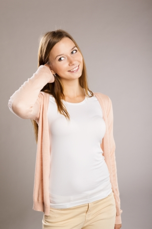 Beautiful young woman posing in studio over a gray background photo