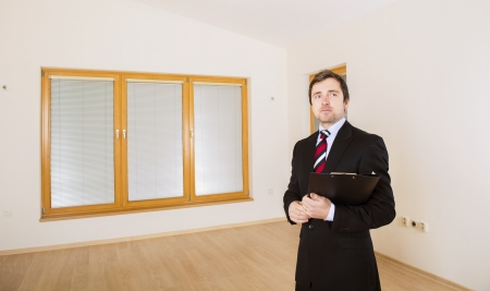 accommodation broker: Real Estate Agent is standing in new empty house  Stock Photo