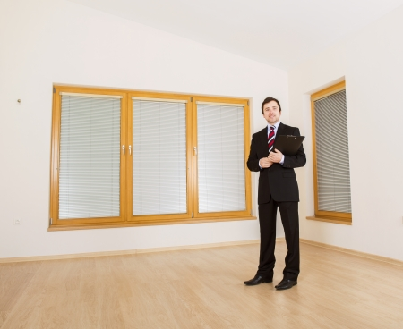Realtor: Real Estate Agent is standing in new empty house  Stock Photo