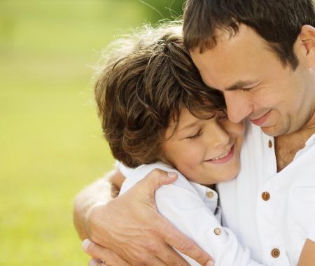 Padre e hijo abrazos y jugar juntos en el parque verde Foto de archivo