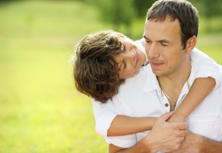 Father and son hugging and playing together in green park