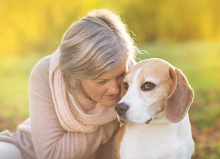 mujer con perro: Mujer mayor que abraza a su perro beagle en el campo