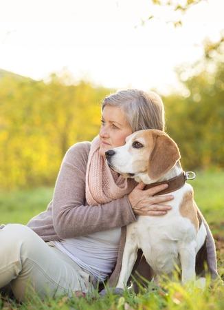 Senior woman hugs her beagle dog in countryside photo