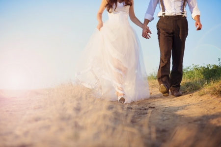 Bride and groom walk in summer nature photo