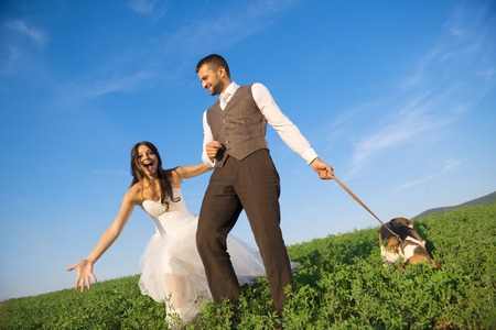 Bride and groom walk with dog in summer nature photo