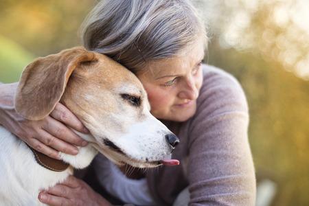 Senior vrouw koestert haar beagle hond op het platteland