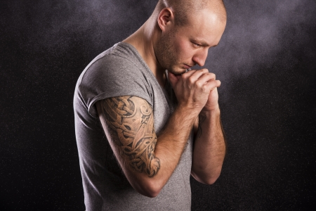 bald man: Handsome young man with tattoo, isolated on black  Stock Photo