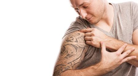 Beau jeune homme avec un tatouage, isolé sur blanc