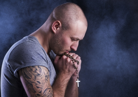 forgiveness: Handsome young man with tattoo, isolated on black  Stock Photo