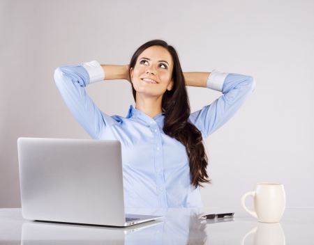 Portret van zakelijke vrouw zit op haar bureau werkt met laptop geïsoleerd op een grijze achtergrond