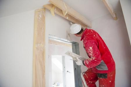 Stavební dělník je malování zdi v novém domě Reklamní fotografie