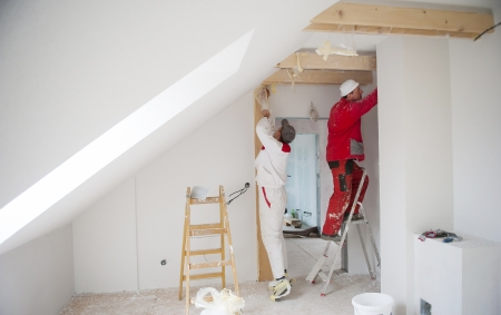 RENOVATE: Construction worker is painting the wall in new house