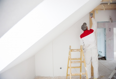 plasterer: Construction worker is painting the wall in new house