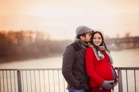 parejas de amor: Retrato de joven pareja embarazada en la ciudad de invierno