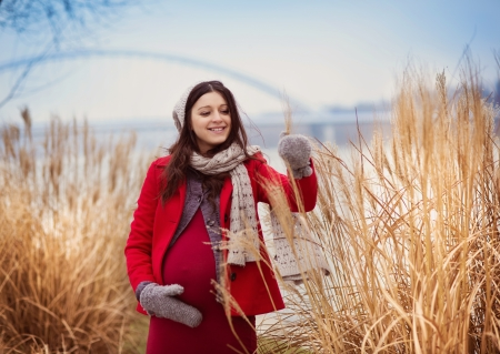 Winter outdoor portrait of pregnant woman in fashionable clothes  photo