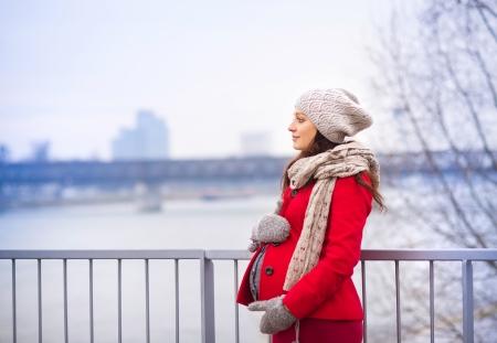 falda: Invierno retrato al aire libre de la mujer embarazada en la ropa de moda de pie junto al río Foto de archivo