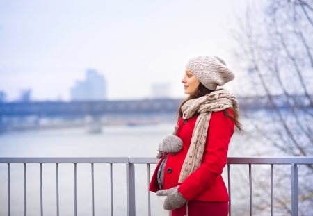 Winter outdoor portrait of pregnant woman in fashionable clothes standing by the river photo
