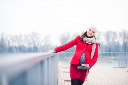 妊娠中の女性は川のそばに立って、流行の服で冬の屋外のポートレート