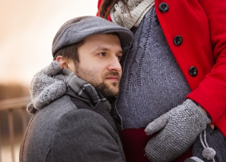 Couple holding pregnant belly in winter country photo