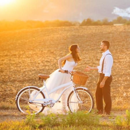 casamento: Retrato de casamento bonito da noiva e do noivo com a bicicleta branca