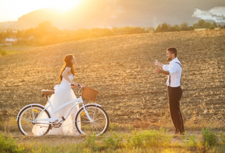 Beautiful bride and groom wedding portrait with white bike photo