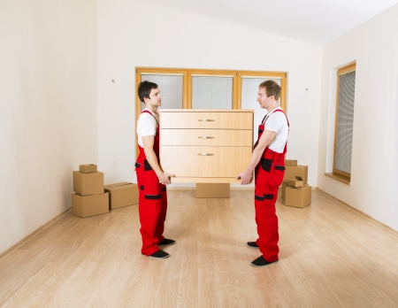 Movers in new house with lot of boxes behind them  photo