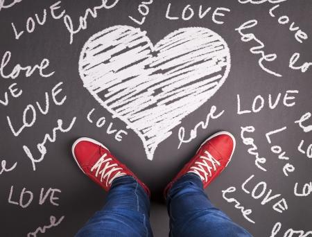 manos y pies: Símbolo simple concepto de amor con zapatillas rojas y tiza dibujado Foto de archivo