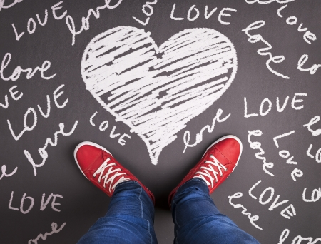 Simple love concept with red sneakers and chalk drawn symbol