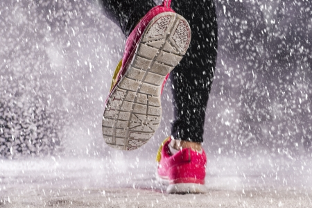 Athlete woman is running during winter training outside in cold snow weather  Stock Photo