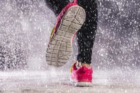 Mujer deportista se ejecuta durante el entrenamiento de invierno al aire libre en clima frío nieve