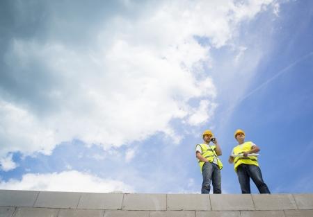 roof beam: Construction Contractors building a big new home Stock Photo