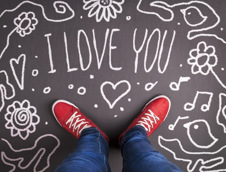 Simple love concept with red sneakers and chalk drawn symbol  photo